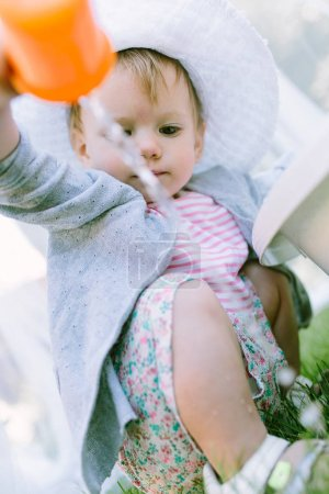 little girl playing with cup
