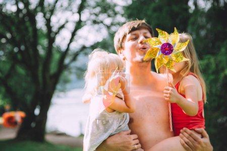 Photo pour Portrait de famille de père heureux avec deux adorables petites filles s'amusant ensemble dans le jardin d'été - image libre de droit