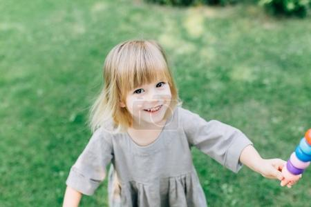 Photo for Portrait of adorable smiling little girl playing with toy outdoor - Royalty Free Image