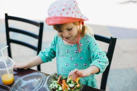 little girl eating salad