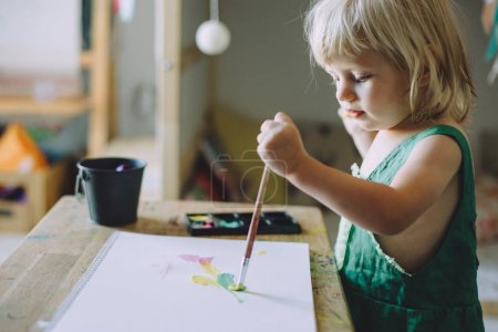cute toddler girl drawing with paints, happy childhood concept