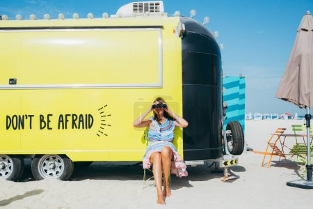 beautiful natural blonde woman at beach looking through binoculars, leaning on trailer