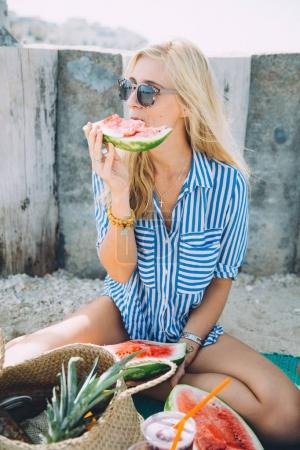 portrait of young beautiful woman eating watermelon at summer picnic