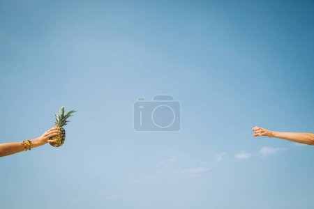 woman giving pineapple fruit to another woman against blue sky