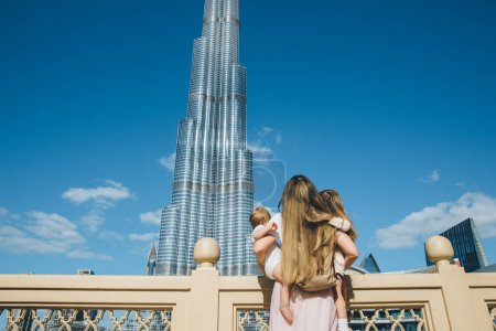portrait of happy beautiful mother with her adorable little daughters contemplating amazing Arabic architecture, Burj Khalifa tower against blue sky, Dubai, UAE