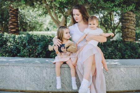portrait of happy beautiful mother with her adorable little daughters relaxing in park