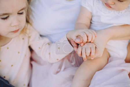 Photo for Portrait of happy mother with her adorable little daughters, hands together - Royalty Free Image