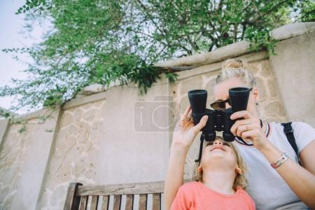 young woman with her cute little son sightseeing with binoculars in Dubai, UAE