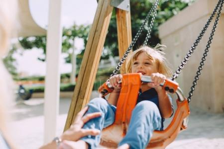 portrait of adorable little boy having fun on swing at playground