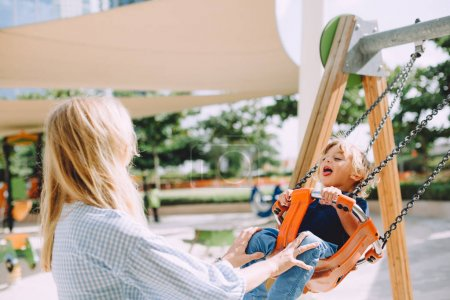 portrait of mother and little boy having fun on swing at playground