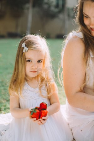 Photo for Cute little girl holding strawberries near her mother at summer picnic in park - Royalty Free Image