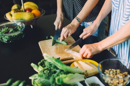 Photo for Two women cutting fresh vegetables for green veggie salad, healthy food cooking - Royalty Free Image