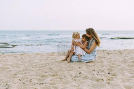 young mother with cute little daughters posing at sandy ocean beach, back view