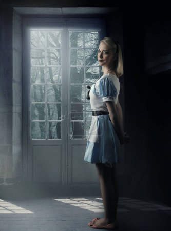 fairy tale . Beautiful girl  wearing a blue dress thinking in a room