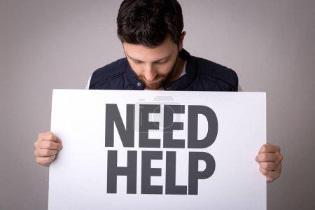 Photo pour Homme tenant papier avec signe, besoin d'aide - image libre de droit