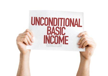 Photo pour Mains sur papier avec signe de revenu de base inconditionnel - image libre de droit