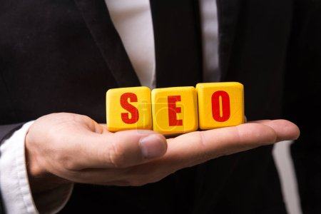 Hand holding a cube with the text: SEO (search engine optimization)