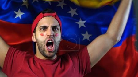 Photo pour Guy vénézuélien agitant un drapeau Venezuela - image libre de droit