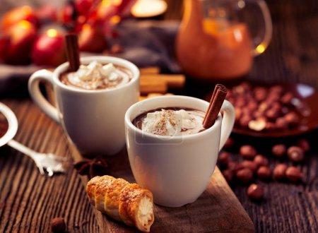 Photo pour Chocolat chaud à la crème fouettée, saupoudré de cannelle aromatique dans des tasses blanches, sur une table en bois rustique - image libre de droit