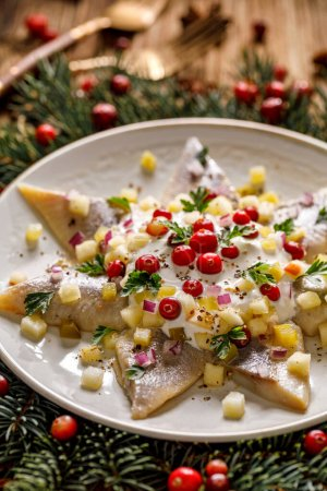 Photo for Christmas Herrings fillets with cream sauce with apple, pickled cucumbers, red onion and spices, garnished with cranberries on a ceramic plate on a festive decorated wooden table, close-up. - Royalty Free Image