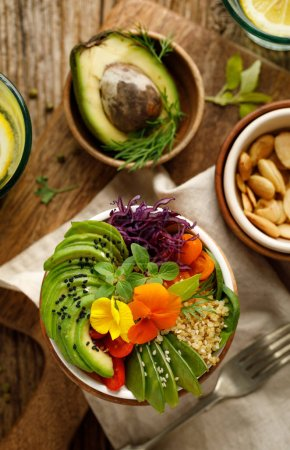 Photo for Buddha bowl of mixed vegetables, quinoa and edible flowers, top view.  Healthy and nutritious vegan meal - Royalty Free Image