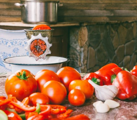 Foto de Antigua amoladora manual vintage y rodajas de tomate fresco, pimiento rojo y ajo sobre la mesa para hacer salsa casera, salsa de tomate - Imagen libre de derechos