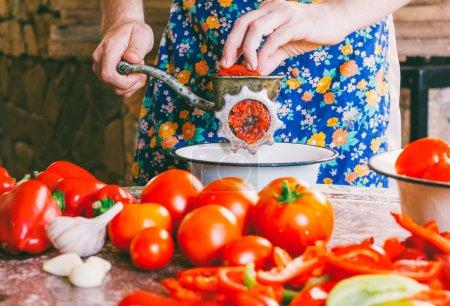 Foto de El hombre cocina salsa casera, salsa de tomate tritura trozos de tomates maduros en una picadora de carne antigua de mano vintage - Imagen libre de derechos