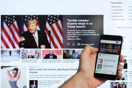 Photo pour Adyguée, Russie - 5 janvier 2018: le fil de nouvelles du populaire site Yahoo Yahoo moteur de recherche sur l'écran du smartphone chinois romaric dans la main mâle - image libre de droit