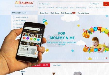 Photo pour Aliexpress sur le marché mondial avec des produits de fabricants de la Chine sur l'écran d'un smartphone et romaric sur l'écran d'ordinateur - image libre de droit
