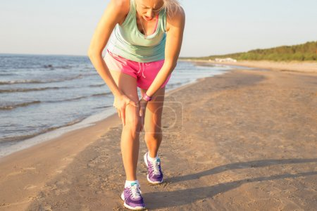Fitness woman having pain in her knee