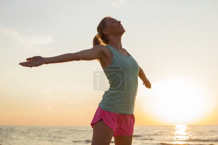 Photo pour Femme heureuse et en forme, en méditant sur la plage - image libre de droit