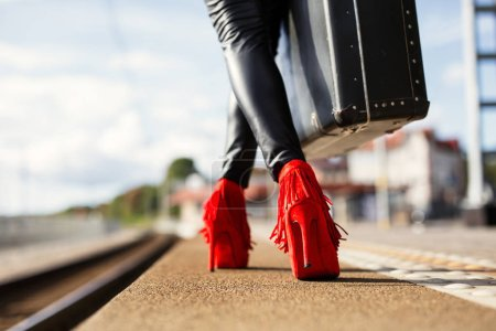 Foto de Mujer con tacones rojos y una maleta en la estación de tren - Imagen libre de derechos