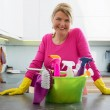 Happy housewife with cleaning supplies...