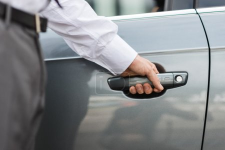 Businessman opening a car door