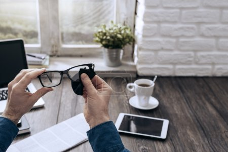 Photo for Man sitting at desk at home and cleaning his glasses with a cloth - Royalty Free Image