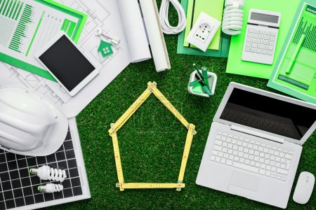 Photo for House project, tools, laptop and solar panel on a grass desktop, folding meter composing a house at center, green building concept - Royalty Free Image