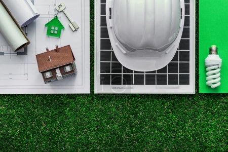 Foto de Edificación sostenible y el concepto de ahorro de energía: proyecto de la casa, el panel solar y herramientas de trabajo en el césped, superior ver - Imagen libre de derechos