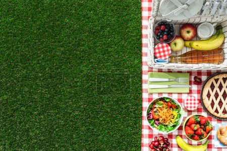 Photo for Picnic at the park on the grass: tablecloth, basket, healthy food and accessories, top view - Royalty Free Image