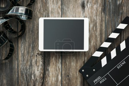 Photo for Digital tablet, clapper and filmstrip on a wooden desktop: cinema and entertainment concept - Royalty Free Image