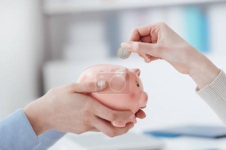 Photo pour Conseiller financier détenant une tirelire et client en insérant une pièce de monnaie: investissements, plan d'épargne et retraite financent concept - image libre de droit