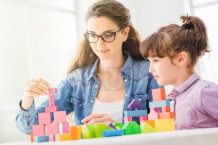 Photo for Young mother and child playing together at home with colorful toy wood blocks, family and leisure concept - Royalty Free Image