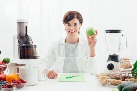 Smiling nutritionist holding an apple