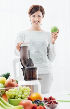 Photo for Smiling young woman holding a fresh apple and using a juice extractor, she is preparing healthy drinks with fruit and vegetables - Royalty Free Image