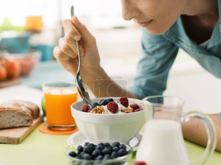 Photo for Woman having an healthy delicious breakfast at home, she is eating yogurt with cereals and fresh fruit, healthy food concept - Royalty Free Image