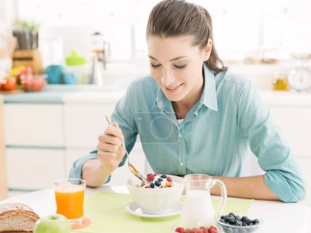 Photo for Smiling happy woman having a delicious healthy breakfast at home, she is eating cereals with fruit and yogurt and sitting at kitchen table - Royalty Free Image