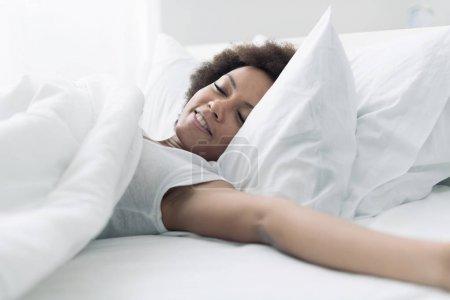 Photo pour Belle femme se réveille dans son lit, elle sourit et s'étire - image libre de droit