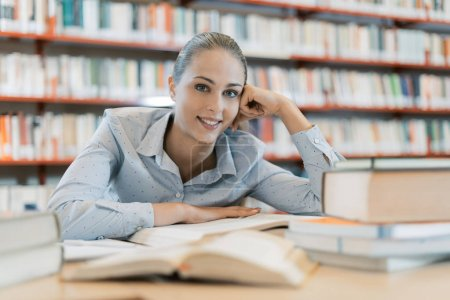Photo for Smiling female student at the library, she is sitting at desk and studying, education and self improvement concept - Royalty Free Image