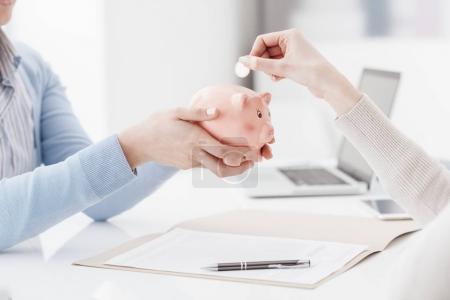 Photo pour Conseiller financier détenant une tirelire et client en insérant une pièce de monnaie: dépôt, d'épargne et de retraite financent concept - image libre de droit