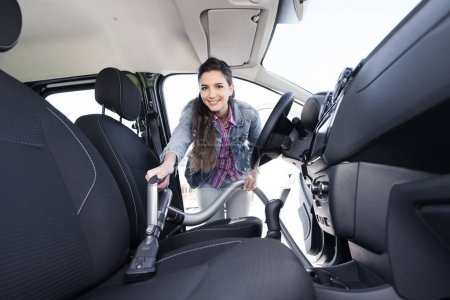 Woman cleaning the car interiors