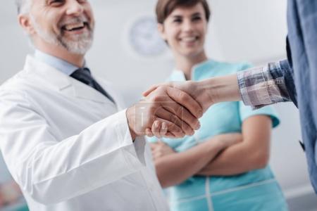 Photo pour Le personnel médical accueille un patient à la clinique : le médecin donne une poignée de main et sourit, le service médical et le concept des professionnels de santé, les mains rapprochées - image libre de droit